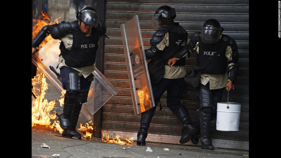 A police officer runs from a fire set off by a Molotov cocktail thrown by protesters in Caracas on April 17.