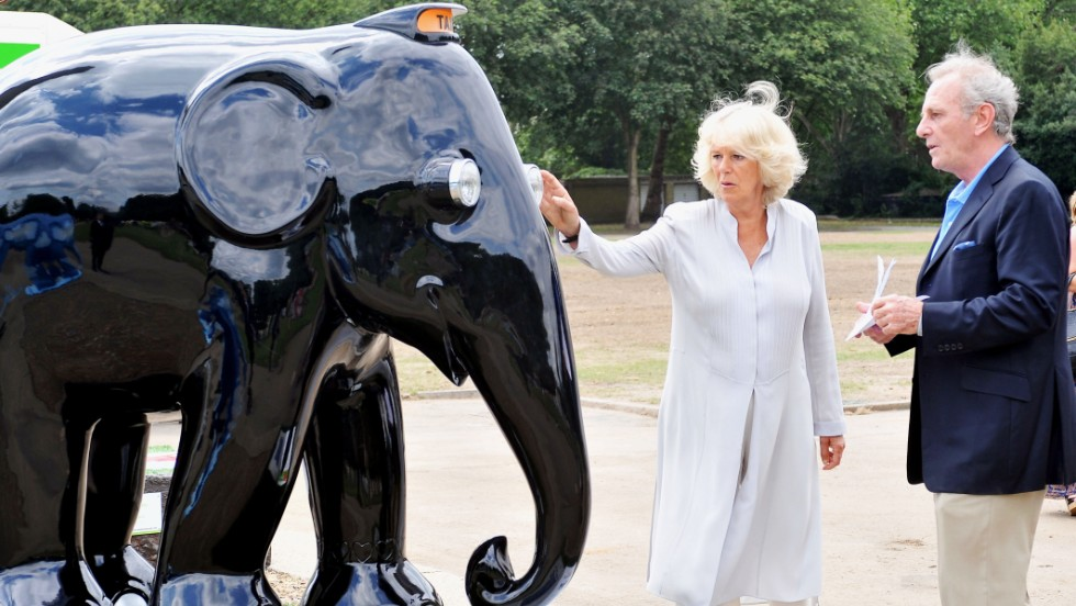 Camilla, Duchess of Cornwall, and her brother, Mark Shand, check out an elephant sculpture designed in the style of a London taxi at the Elephant Parade exhibition at Chelsea Hospital Gardens in London on June 24, 2010.