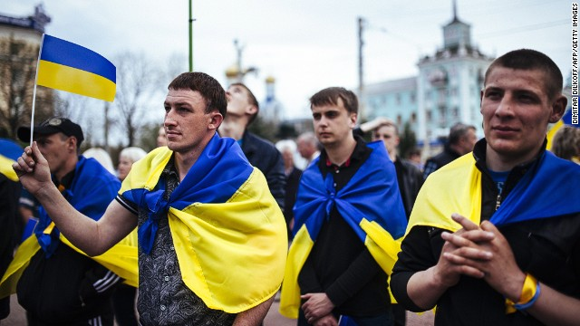 People draped in Ukrainian flags attend a pro-Ukrainian rally in the eastern Ukrainian city of Lugansk on April 19, 2014.