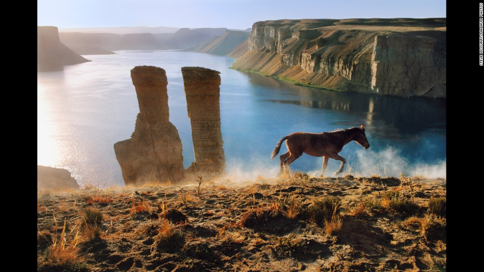 A colt runs after its mother past two vertical rock formations in Band-i-Amir, 2002.