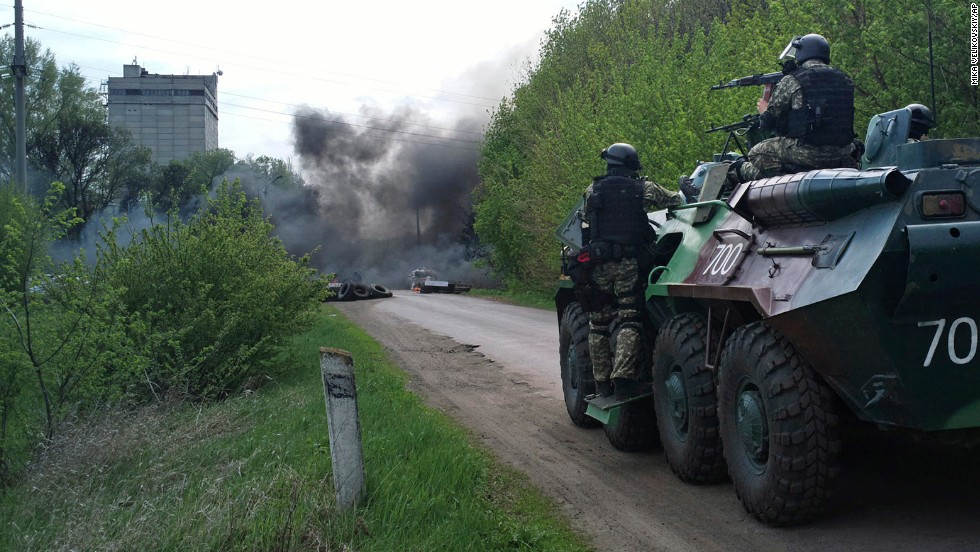 Ukrainian troops take position near burning tires at a pro-Russian checkpoint in Slovyansk on Thursday, April 24.