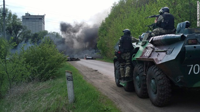 Ukrainian troops take position near burning tires at a pro-Russian checkpoint in Sloviansk following an attack by Ukrainian soldiers on Thursday, April 24.