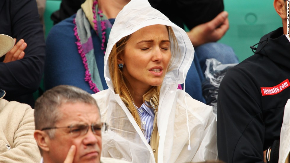 The life of a tennis supporter is not all glamor as a downpour at the French Open leaves Ristic to don protection.