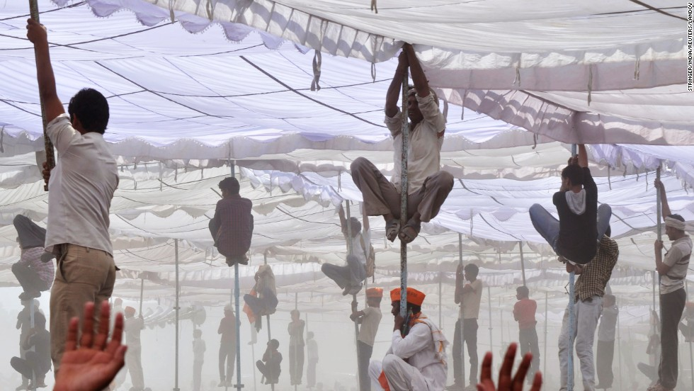 "Supporters of Hindu nationalist Narendra Modi, the prime ministerial candidate for India's main opposition Bharatiya Janata Party, climb up the poles of a temporary tent to get a glimpse of Modi during an election campaign rally in Mathura, India, on Tuesday, April 21. It is the <a href=""http://www.cnn.com/2014/04/06/opinion/bergen-india-elections-11-things/index.html"">largest democratic exercise in history</a> as voters will elect 543 members to the lower house of parliament, which will then select the country's next prime minister. The vote counting will be carried out and concluded on May 16."