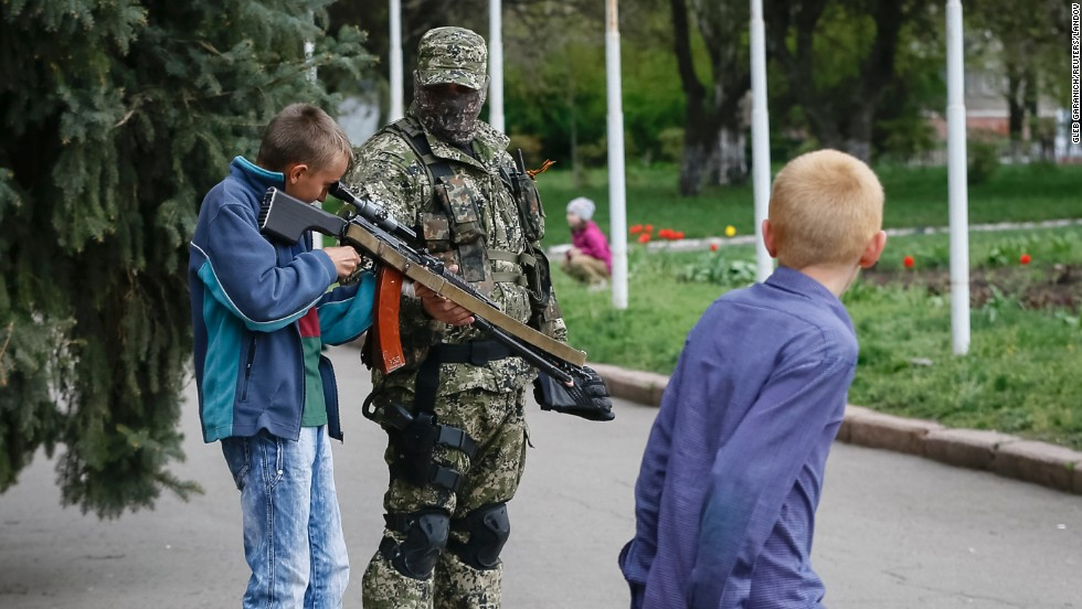 A boy looks through the scope on a machine gun as a pro-Russian armed man stands guard outside the mayor's office in Slaviansk, Ukraine, on Sunday, April 20.