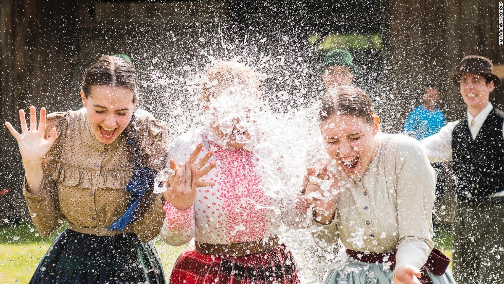 Women in traditional costumes are sprayed with water by men as members of the Margaretha Dance Group perform in the Museum Village in Nyiregyhaza, Hungary, on Monday, April 21.