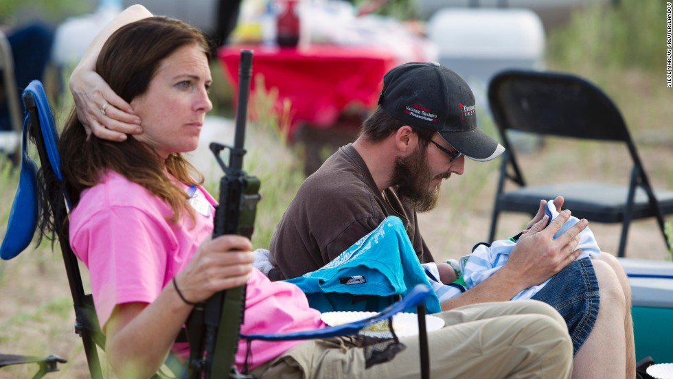 "Chris Shelton of Las Vegas interacts with his 1-week-old son as his mother Shelley Shelton holds his rifle during a Bundy family ""Patriot Party"" near Bunkerville, Nevada, on April 18."