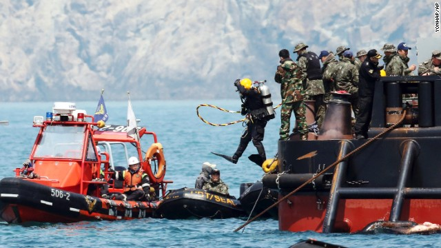 A diver jumps into the sea to look for people believed to have been trapped in the sunken Sewol ferry near buoys which were installed to mark the vessel in the water off the southern coast near Jindo, South Korea, Friday, April 25, 2014. Frustrated relatives of the scores of people still missing from the sinking of the ferry staged a marathon confrontation with the fisheries minister and the coast guard chief, surrounding the senior officials in a standoff that lasted overnight and into Friday morning as they vented their rage at the pace of search efforts.(AP Photo/Yonhap) KOREA OUT