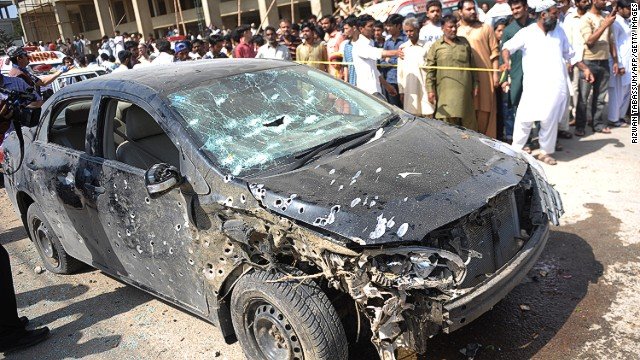Pakistani residents gather beside the wreckage of a car after a bomb explosion in Karachi on April 25, 2014.