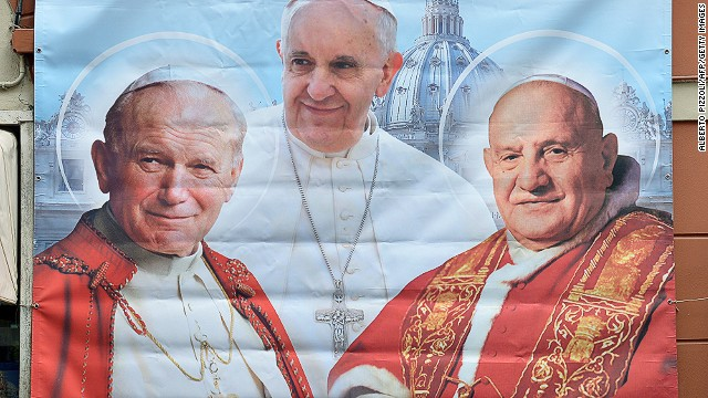 A poster showing Pope Francis middle pope John Paul II (L) and Pope John XXIII (R), that will be canonized next Sunday, is seen in Borgo Pio street near the Vatican during the pontiff weekly general audience in St. Peter's square on April 23, 2014.
