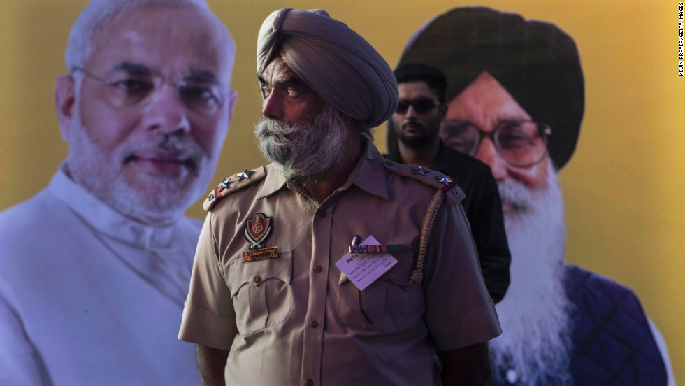 An Indian Punjab State Police officer stands in front of a picture of Bharatiya Janata Party leader Narendra Modi and Punjab Chief Minister Parkash Singh Badal during an election rally by the two men April 25 in Bathinda, India.