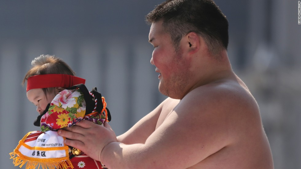 "A sumo wrestler holds a colorful contestant. <em>Naki-zumo</em> is a tradition that goes back more than 400 years, according to <a href=""http://www.japantimes.co.jp/culture/2012/05/04/events/babies-set-to-tear-up-the-ring/#.U1wjc8_D-Um"" target=""_blank"">The Japan Times</a>."