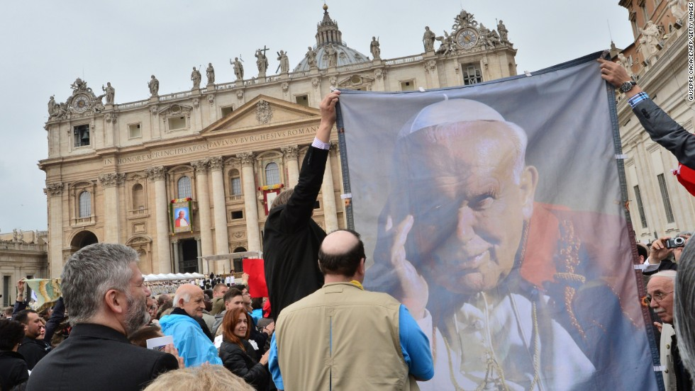 Pilgrims hold up a banner showing Pope John Paul II during the canonization Mass at the Vatican on April 27.
