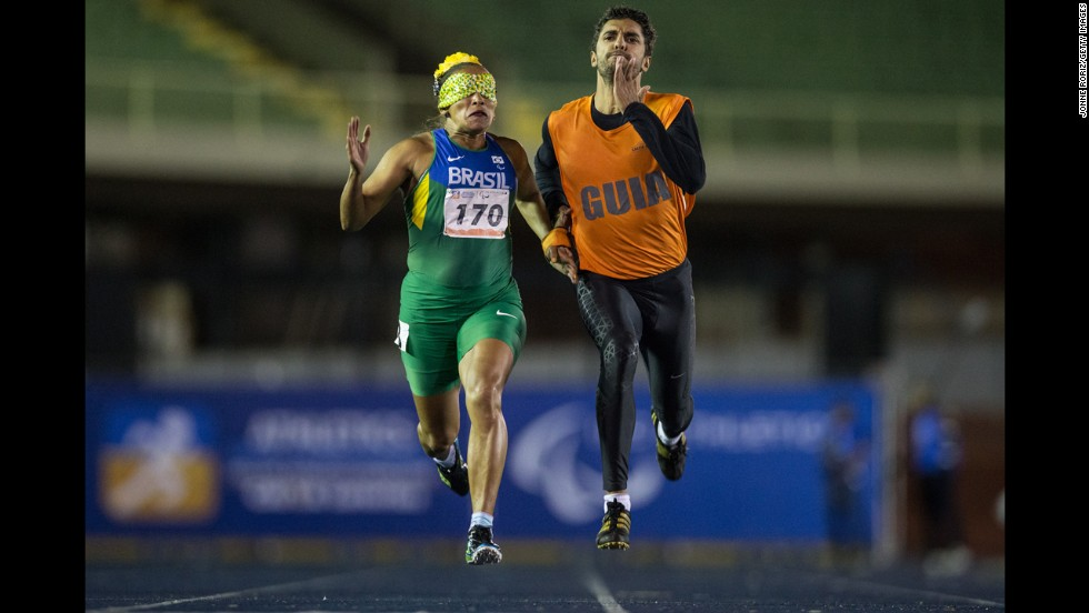Sprinter Terezinha Guilhermina competes in the 200 meters along with her guide, Guilherme Santana, during the T11 final of the Loterias Caixa Brazilian Athletics Open Championships on Thursday, April 24. The T11 category is for athletes who are visually impaired.