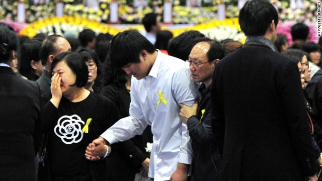 Students rescued from the sunken South Korean ferry 'Sewol', wearing white shirts, pay tribute at the state-controlled joint memorial altar for the dead in Ansan on April 30, 2014