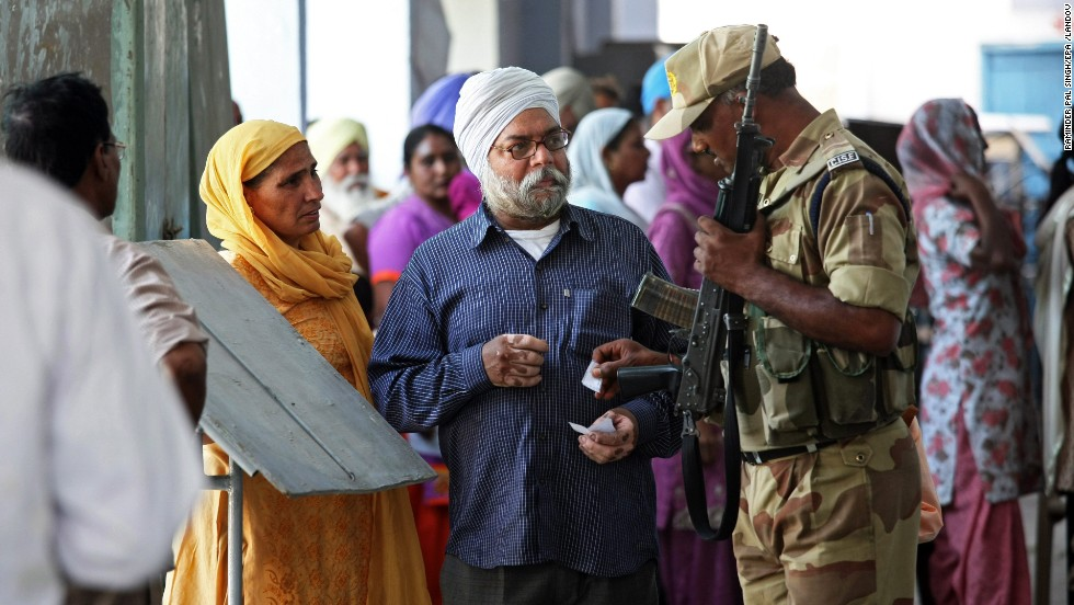 A soldier helps voters locate their polling station in the village of Sultanwind, near Amritsar, India, on April 30.