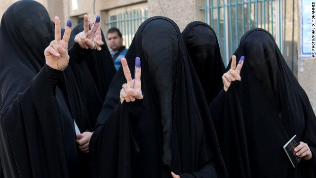 Iraqi women give victory signs while showing their inked fingers after voting in Baghdad on Wednesday.