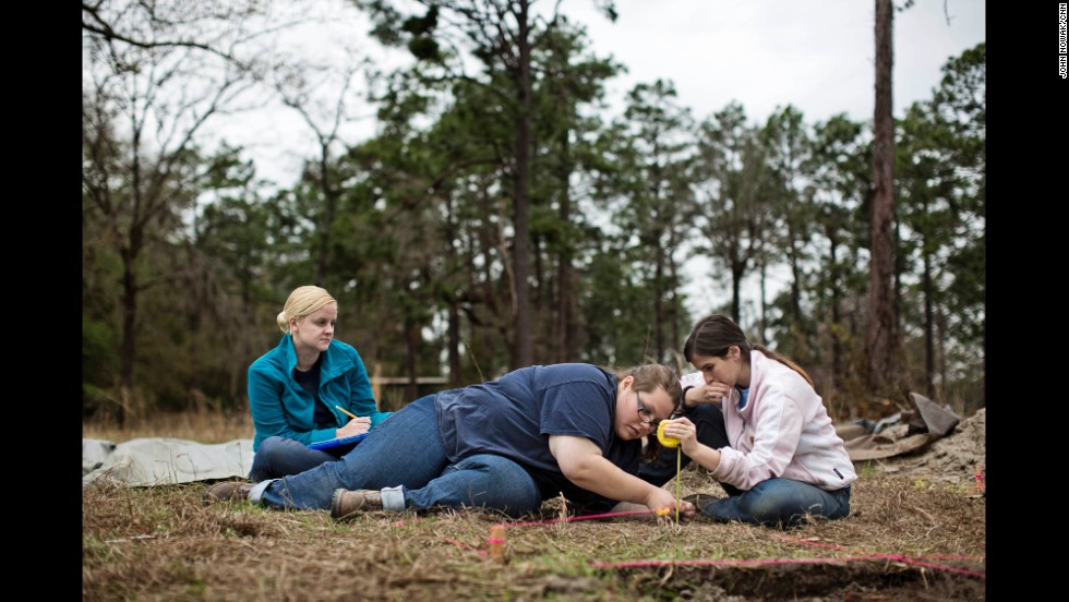 "From left, Georgia Southern students Amanda Andreu, Amanda Shively, and Kylie Jones measure an excavation site in the part of the prison where about 10,000 Union soldiers were held captive during the Civil War.  Jones said this semester was her first field school, at which she learned proper archeological techniques. ""It makes the past more real,"" she says of the effort."
