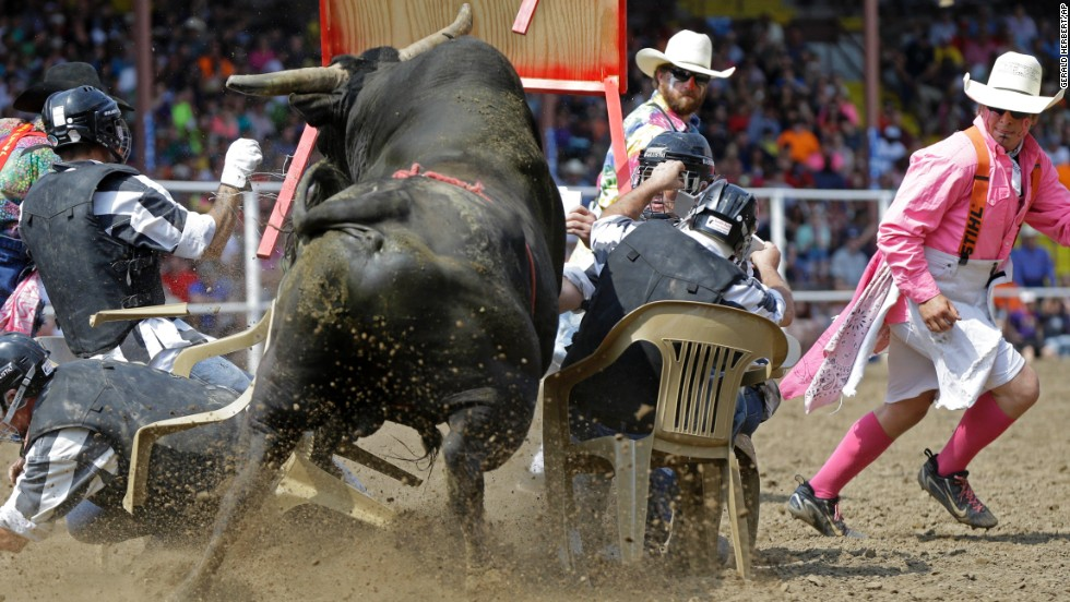 "A bull rams a card table Saturday, April 26, during the ""convict poker"" portion of the Angola Prison Rodeo in Angola, Louisiana. It is the longest-running prison rodeo in the United States."