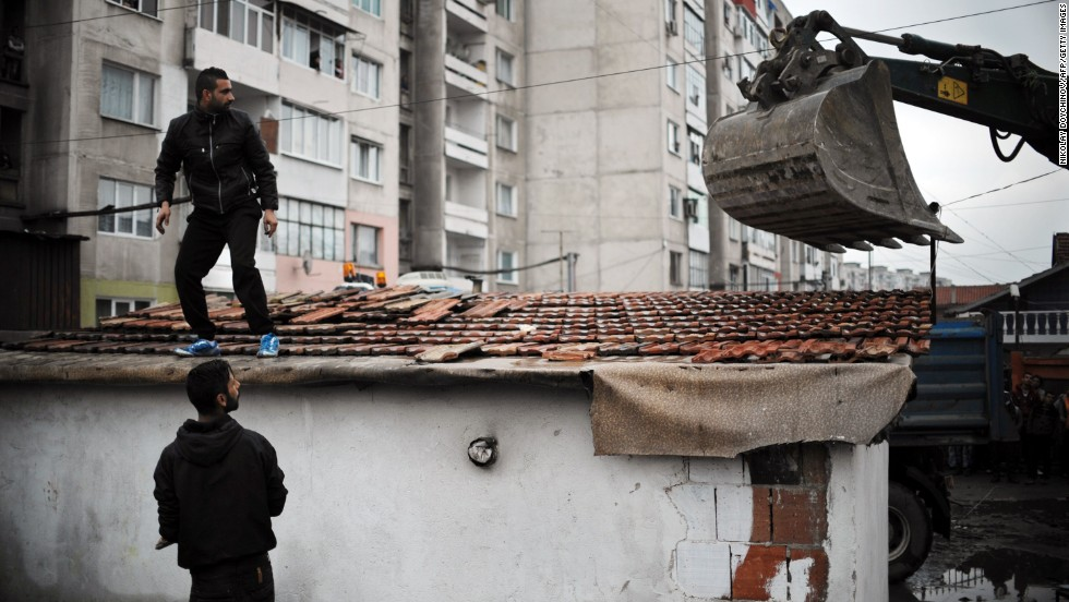 Men watch as equipment demolishes a house in a Roma section of Plovdiv, Bulgaria, on Friday, April 25. About 50 illegal buildings in the Roma neighborhood were destroyed.