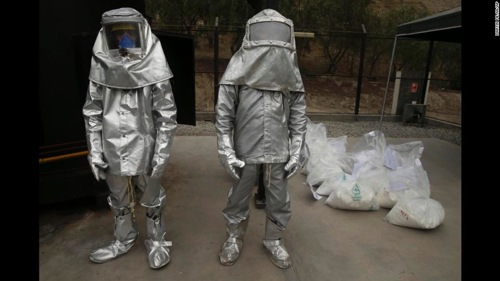 Workers dressed in special heat-reflecting suits stand next to bags of seized cocaine that were set to be destroyed at a Lima, Peru, police base on Tuesday, April 29. Police say they burned more than 11 tons of drugs, including cocaine, marijuana, opium and heroin.