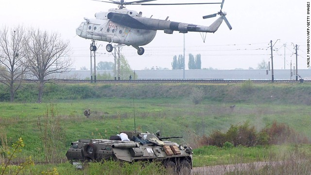 A helicopter lands near a tank at a checkpoint seized in the early morning in the village of Andreevka, 7 km from the center of the southern Ukrainian city of Slavyansk, on May 2, 2014.