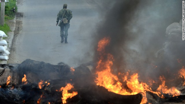 An armed pro-Russian man walks past burning debris at a checkpoint in the southern Ukrainian city of Slavyansk on May 2, 2014. Ukraine's military lost two helicopters and two servicemen on May 2 in a deadly offensive launched just before dawn against pro-Russian rebels holding the flashpoint town of Slavyansk, insurgents and authorities said.