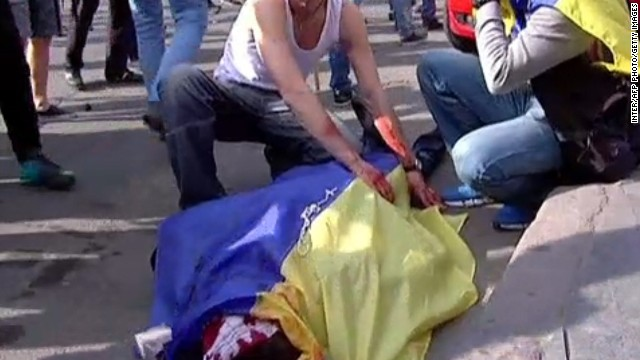 TV images released by INTER, shows a man covering the bloodied body of a man with an Ukrainian flag during a demonstration on May 2, 2014 in Odessa.