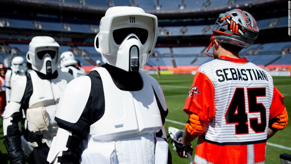 """Star Wars"" fans dress in costume on May the 4th annually as a play on the phrase ""May the force be with you."" Here, stormtroopers cross paths with lacrosse player Domenic Sebastiani of the Denver Outlaws before a game against the Ohio Machine in Denver, Colorado. The teams wore ""Star Wars""-themed jerseys. Click through the gallery for more costumes."