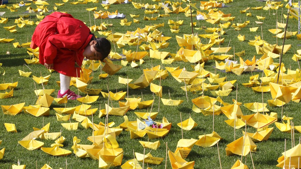 MAY 5 - SEOUL, SOUTH KOREA: A young girl reads messages written on paper boats for the victims of the sunken ferry Sewol at a memorial altar. A total of 242 people, many of them schoolchildren, are known to have died when the ship sank en route to the resort island of Jeju on April 16; 60 others are still missing.