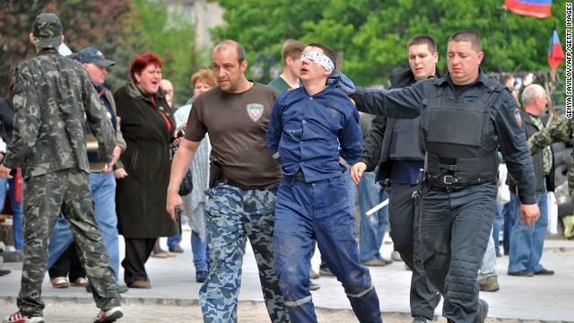 Pro-Russian militants take away a man outside the regional state building they seized in Donetsk on May 5, 2014.