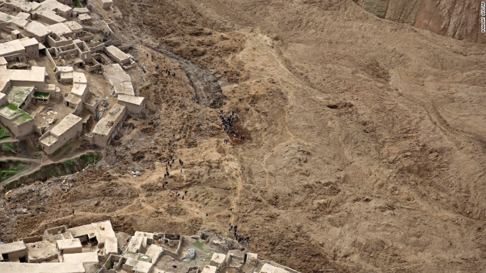 Afghans walk near the site of the landslide on May 5.