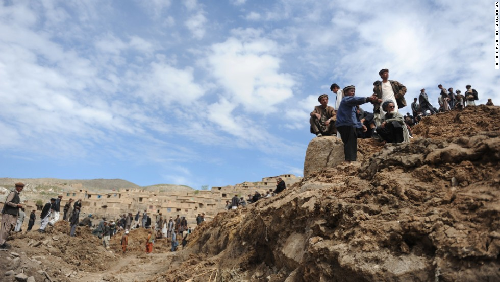 Afghan villagers search through dirt and debris at the scene of the landslide on May 5.