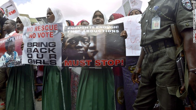 "A policeman stand beside children holding as members of Lagos based civil society groups hold rally calling for the release of missing Chibok school girls at the state government house, in Lagos, Nigeria, on May 5, 2014. Boko Haram on Monday claimed the abduction of hundreds of schoolgirls in northern Nigeria that has triggered international outrage, threatening to sell them as ""slaves"". ""I abducted your girls, "" the Islamist group's leader Abubakar Shekau said in the 57-minute video obtained by AFP, referring to the 276 students kidnapped from their boarding school in Chibok, Borno state, three weeks ago."