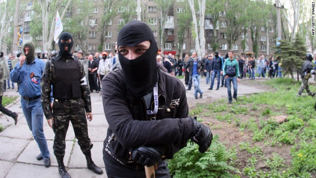 Masked pro-Russian activists stand outside the district state building after seizing it in the eastern Ukrainian city of Donetsk on May 4, 2014.