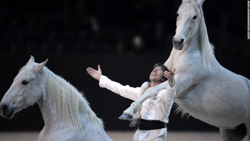 French horse trainer Jean Francois Pignon performs with horses at the opening ceremony for the FEI World Cup jumping and dressage finals in Chassieu, France.