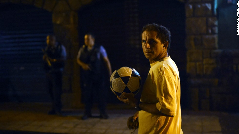 A man walks past with a football in his hand as Brazilian Police Special Forces stand guard in the background during a violent protest in a favela near Copacabana.