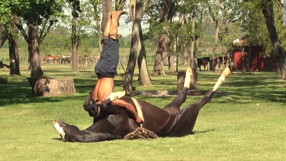 A wrangler performs yoga-esque poses atop a horse at the Doma India horse taming school in San Luis, Argentina.