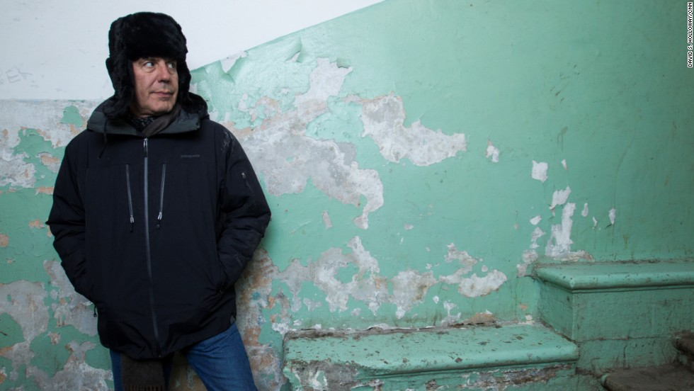 Bourdain stands in the entryway of a community apartment complex called the House of Moruzi. It is a holdover from the Cold War era and contains several large rooms that are rented by individuals who share common spaces like kitchens and bathrooms.