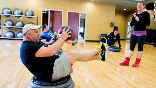 CNN Fit Nation coach April Gellatly, right, helps Ron Cothran work his core during Kick-off Weekend in Atlanta.