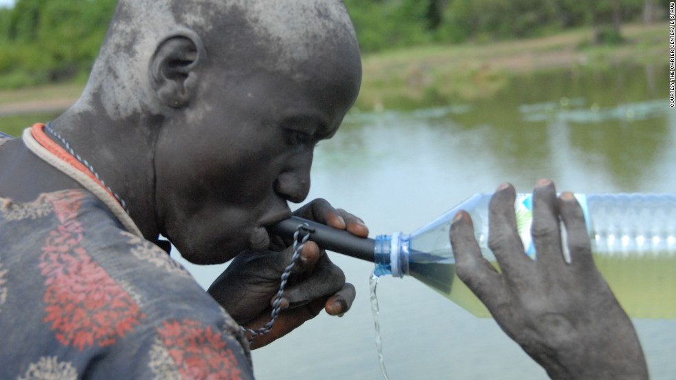A Southern Sudanese man uses a pipe filter to strain out possible water fleas, which could contain Guinea worm larvae, from a potentially contaminated water source.