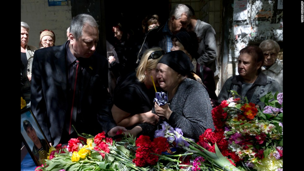 The mother of Dmitriy Nikityuk, who died in a fire at a trade union building during riots in Odessa, Ukraine, cries next to his coffin during his funeral on Thursday, May 8.