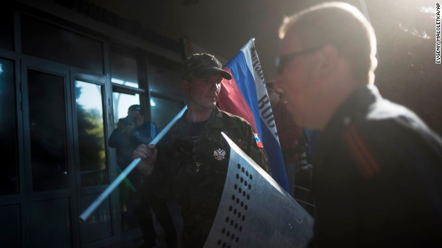 A pro-Russian activist stands with a Russian national flag outside the regional Interior Ministry building in Luhansk, Ukraine, on Wednesday, May 7.