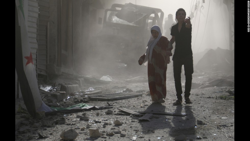 A man helps a woman through debris after reported airstrikes by government forces on Thursday, May 1, in the Halak neighborhood of Aleppo.