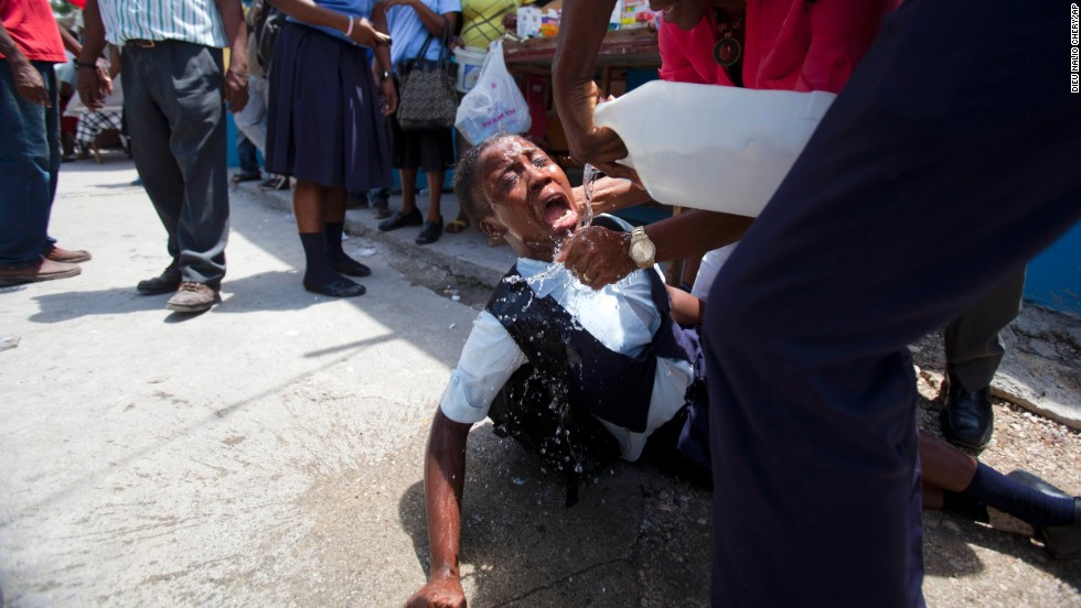 A student affected by tear gas is helped during clashes between students and the national police Wednesday, May 7, in Port-au-Prince, Haiti. Students were calling for authorities to respond to their striking teachers' demands for higher pay and improved working conditions.
