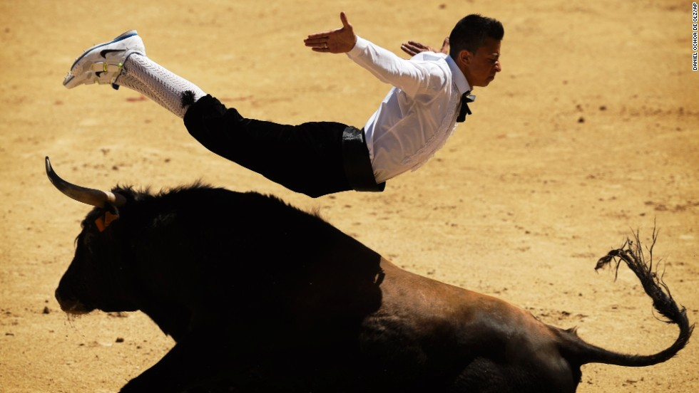"A ""recortador"" jumps over a bull in Madrid on Friday, May 2. ""Recortadores"" is a bloodless type of bullfighting where the performers acrobatically leap over bulls and the ones who get the closest and show the least amount of fear are the winners."
