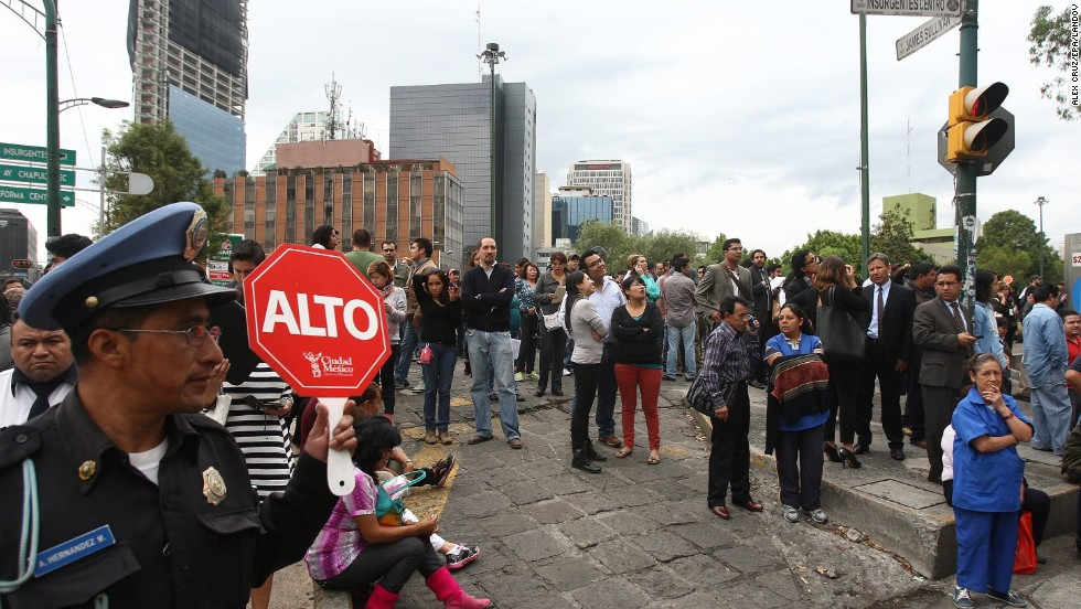 People stand in the street in Mexico City after evacuating nearby buildings.