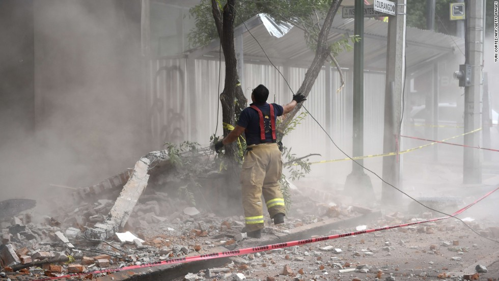 A firefighter works to demolish a damaged wall in Mexico City.