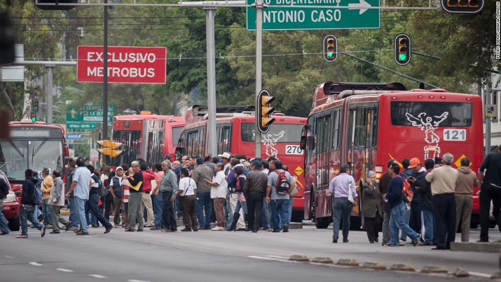 People line the streets amid stopped traffic in Mexico City.