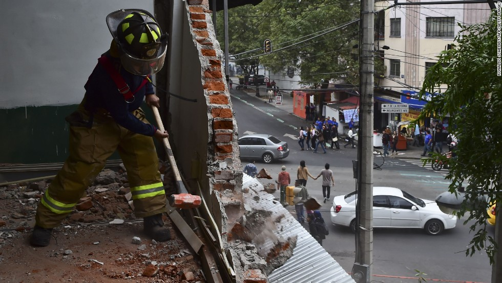 A fireman in Mexico City uses a sledgehammer to demolish a wall damaged in the earthquake.